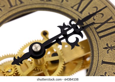 Close up of old-fashioned wall clock with visible gears, isolated on white background. Intentional shallow depth of field. Studio work.