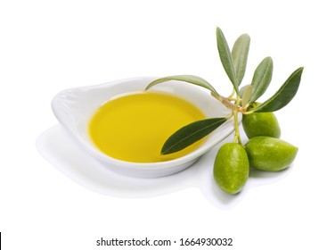Close up of olive oil in a white ceramic bowl and branch of olive tree with green fruits and leaves,  isolated on white background.