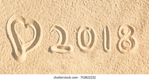 Close up on 2018 written in the sand of a beach with a heart