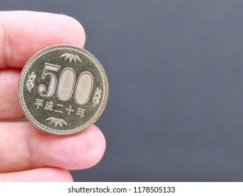 close up on 500 coins with hand holding. Japanese Yen with the copy space for free text