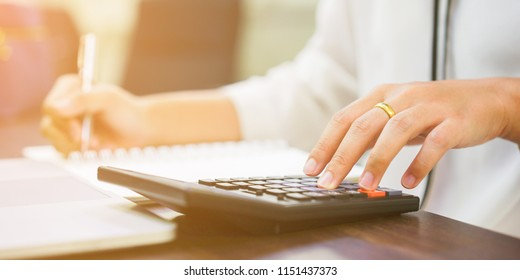 close up on accountant employee woman hand pressing on calculator for calculate cost estimate monthly and writing result to paper , business concept