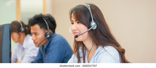 close up on asian call center woman work with diverse ethnic employee at operation monitor room for contact or talking with customer concept.