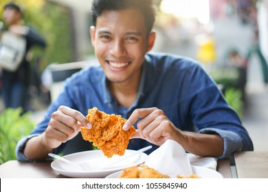 close up on asian man try to eating piece of fried chicken at outdoor restaurant on weekend day with chill time , happy lifestyle concept
