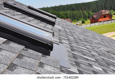 Close up on attic skylight window repair with waterproofing membrane on asphalt shingles roof. Roofing Construction.