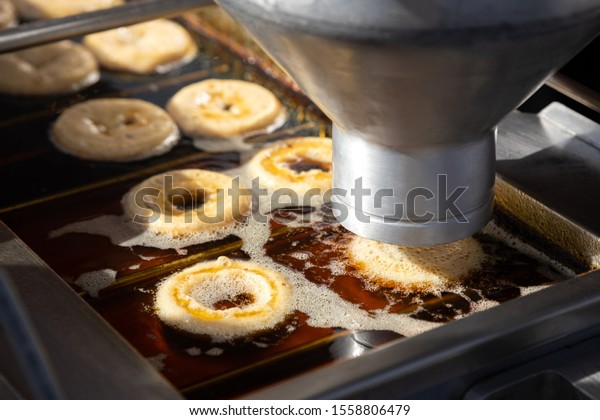 Close up on automatic donut frying machine, with doughnut rings being dispensed into hot oil