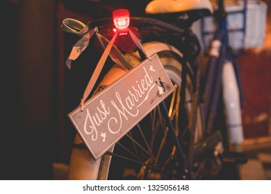 """close up on the back of a bike with a sign """"just married"""" and red light turn on"""