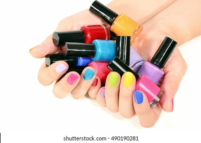 Close up on beautiful woman hands holding many bottles of nail polish and with sexy rainbow manicure.Nail art isolated on white.