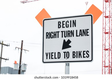 Close up on a Begin Right Turn Lane and Yield To Bikes Sign posted along a Bicycle Lane on a downtown street