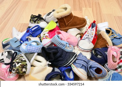 Close up on big pile of baby shoes. Untidy stack of boy and girl toddler shoes thrown on the ground.