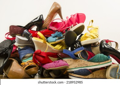 Close up on big pile of colorful woman shoes. Untidy stack of shoes thrown on the ground.
