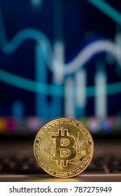 Close up on a Bitcoin token resting on a computer keyboard, in the background the monitor is visible with analytics data.