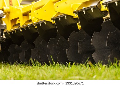 Close up on black disc cultivator for loosening the soil. Agricultural machine parts details.