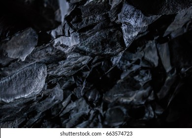 Up close on black volcanic basalt rock formations in the low light of a small cave on the black sand beach at Vik southern Iceland