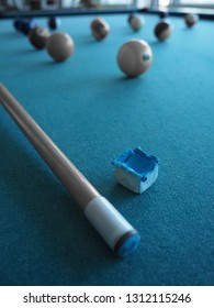 Close up on blue chalk and cue on a billiards table, picture in black and white and monochrome special effect in blue.