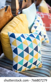 Close up on blue and yellow triangle pattern throw pillows on an outdoor patio chair, with a blue striped cushioned bench