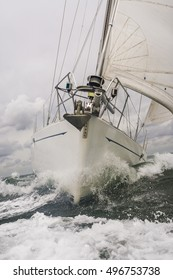 Close up on the bow of a sailing boat or yacht breaking through a wave on a stormy sea