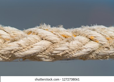 Close up on the braided strands of a rope made of natural jute, sisal or hemp fibres on grey