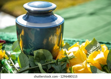 Close up on a burial urn with yellow roses, in a bright cemetery scene, with space for text on the right