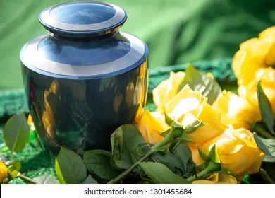 Close up on a burial urn with yellow roses, in a bright funeral scene, with space for text on the right
