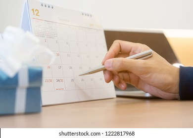 close up on business man hand using pen writing on calendar for note appointment or make a booking special date on timetable with gift at office desk concept.