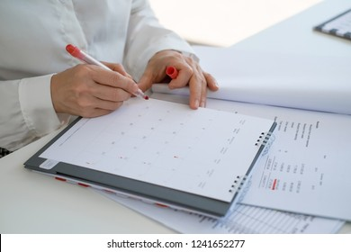 Close up on businesswoman hand with pen writing on calendar for note or make appointment concept.