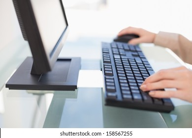 Close up on businesswoman typing on keyboard in bright office