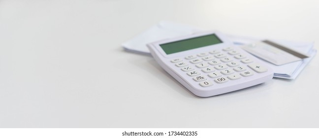 close up on calculator with group of mail letter and credit card at white table for end of the month expense day concept