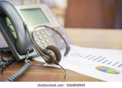 close up on call center headphone laying on telephone and statistic data paper at operation room for business concept