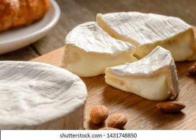 Close up on Camember cheese. Pieces of soft cheese reveal its runny cream texture. Ingredient for puff pastry filling.