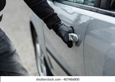 Close up on car thief hand pulling the handle of a car. Car thief, car theft concept