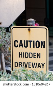"""Close up on a """"Caution Hidden Driveway"""" sign along the driveway of an building parking garage in Vancouver"""