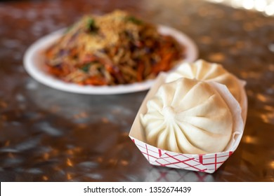 Close up on Chinese baozi dumplings with a chow mien noodle dish in the background, in a restaurant menu item combo