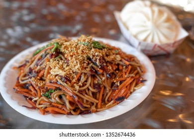 Close up on a chow mien noodle dish with Chinese baozi dumplings in the background, in a restaurant menu item combination