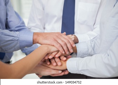 Close up on colleagues hands all together in bright office