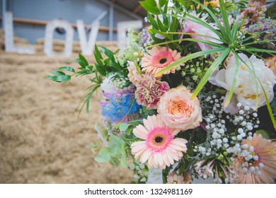 Close up on colorful pastel flower bouquet with LOVE letters placed on a haystack in the background