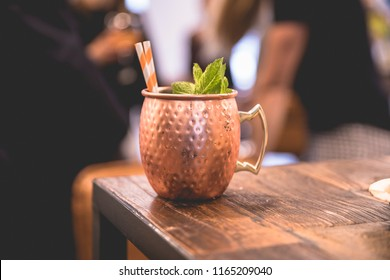Close up on a copper cup with Moscow Mule cocktail, fresh mint as decoration and a white and orange carton straw