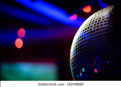Close up on a dark disco ball with red and blue highlights in the blurry background, at a rave party in a bar and club
