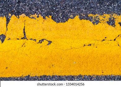 Close up on dark grey asphalt tarmac road with yellow pain line