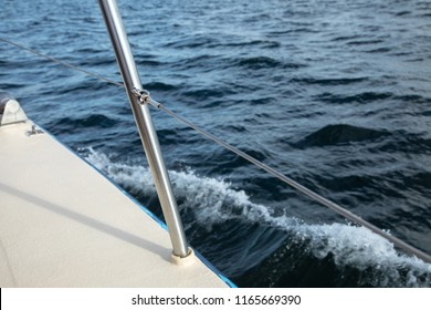 Close up on the deck railing of a luxury sailing yacht with sea waves in the background, and space for text on the right