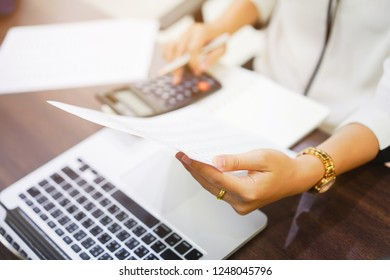 close up on employee woman finger hand holding statement report and press on calculator for summarize company's profit at accounting deaprtment ,working woman concept.