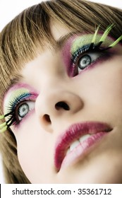 close up on face of beautiful girl with green long eyelashes and color makeup
