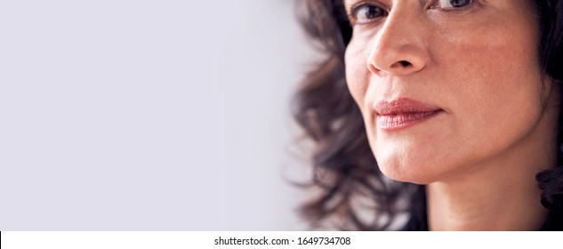 Close Up On Face Of Smiling Mature Woman In Studio