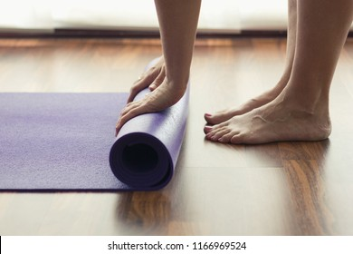 Close up on feet and hands of woman folding purple yoga mat in studio. Female yogi rolling equipment after indoors morning practice. Pilates, workout, healthy lifestyle, exercise, flexibility concepts