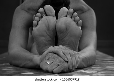 Close up on feet of naked girl practicing paschimottanasana yoga asana. Woman on forward bend pose holding hands. Black and white photography. Flexibility concept