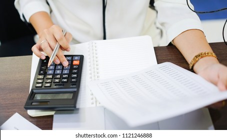close up on finger hand holding statement report and press on calculator for summarize company's profit at accounting deaprtment ,working woman concept.
