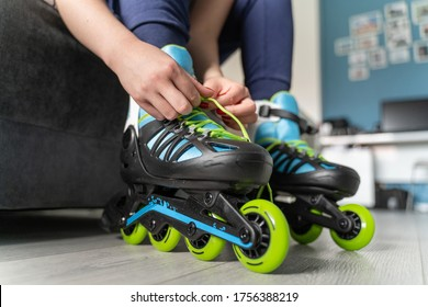 close up on foot of unknown caucasian woman on the floor taking off or putting on the rollerblade inline skates tying laces while sitting on bed at home in day fun freedom motion and youth concept
