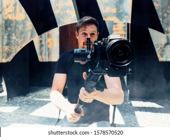close up on the foreground of a professional camera on a gimbal -  a cameraman is recording and broadcasting video footage - blogger, vlogger, storyteller and traveler concept