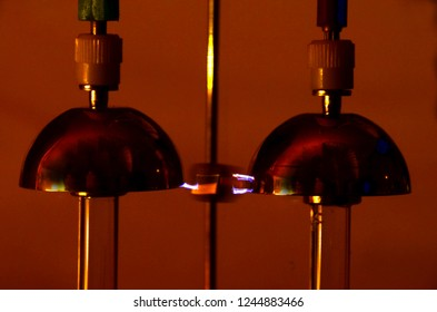 Close up on a Franklin Bell setup, a small hammer swings between two bells, where the voltage difference between the bells is ca 30.000 volts. The electrostatic field makes the hammer swing.