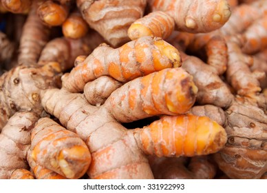 Close up on freshly uprooted turmeric. Turmeric is one of the main ingredients used in most Asian dishes.Image uses selective focusing, may apear blurry and for background purposes only.