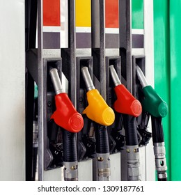 Close up on fuel nozzle in oil dispenser with gasoline and diesel in service gas station.